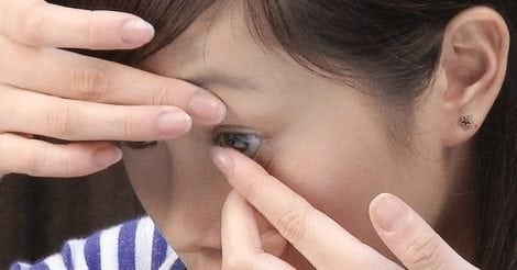 girl putting on contact lens